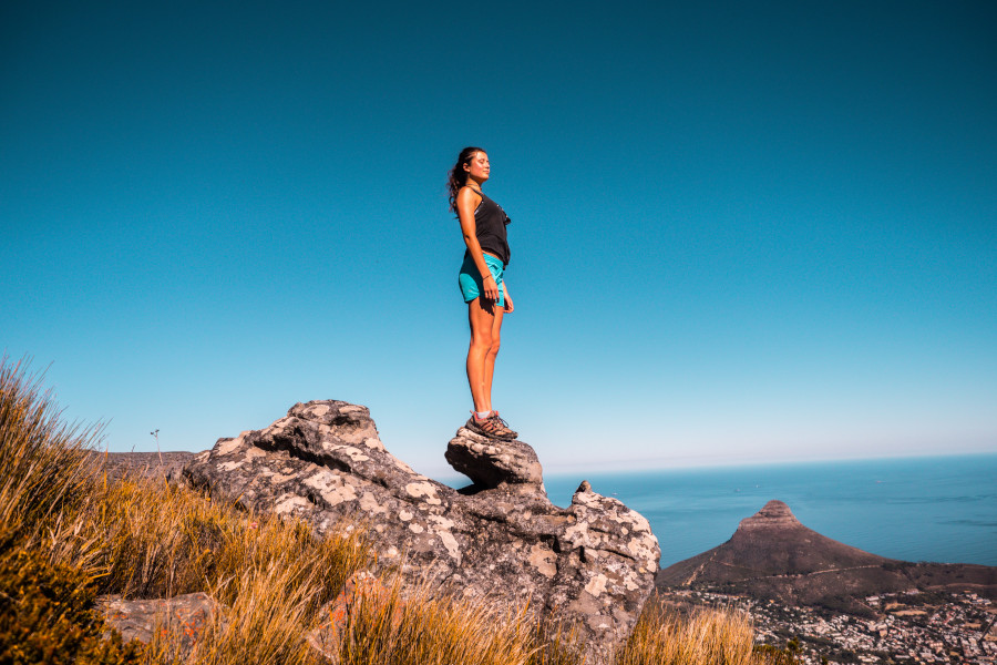 Woman standing on top of cliff against blue sky