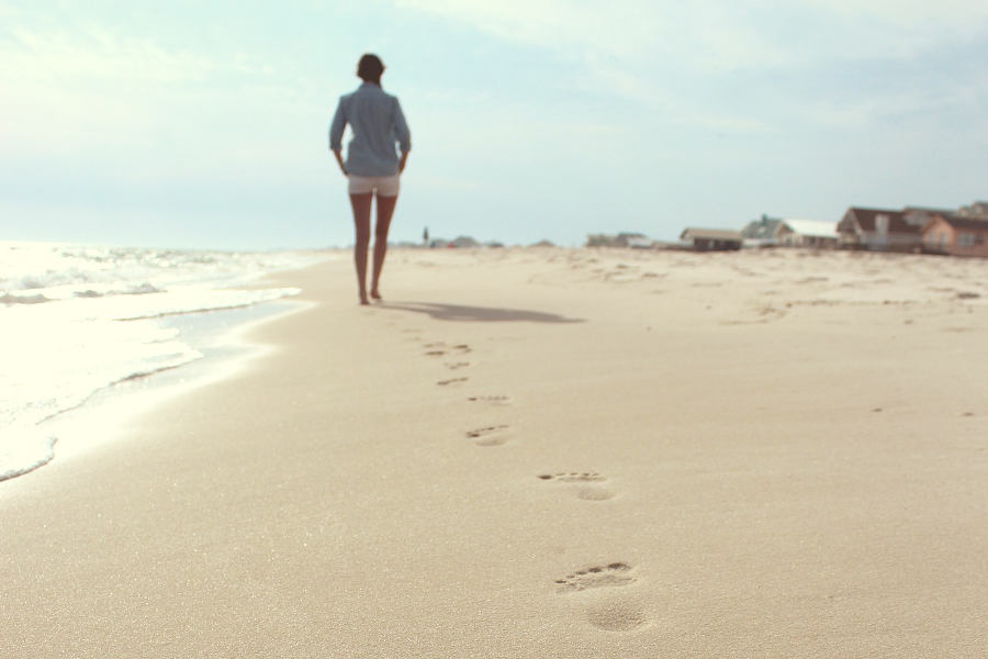 personal retreat: woman taking long walk on the beach